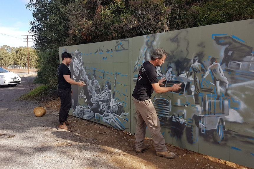 Two men hold spray cans and create art on a green wall.