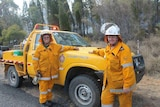 Two women firefighters stand next to a truck at Scrubby Creek