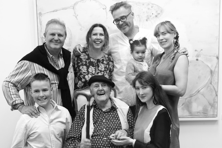 A black and white family portrait featuring eight people