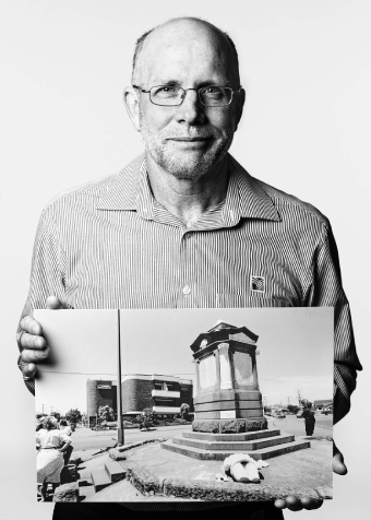 A man posing for a portrait holding an historic photograph.