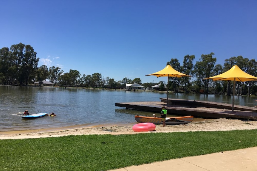 A boy stands beside a kayak on the sand, while two kids are in the Gunbower Creek next to a stand up paddleboard.