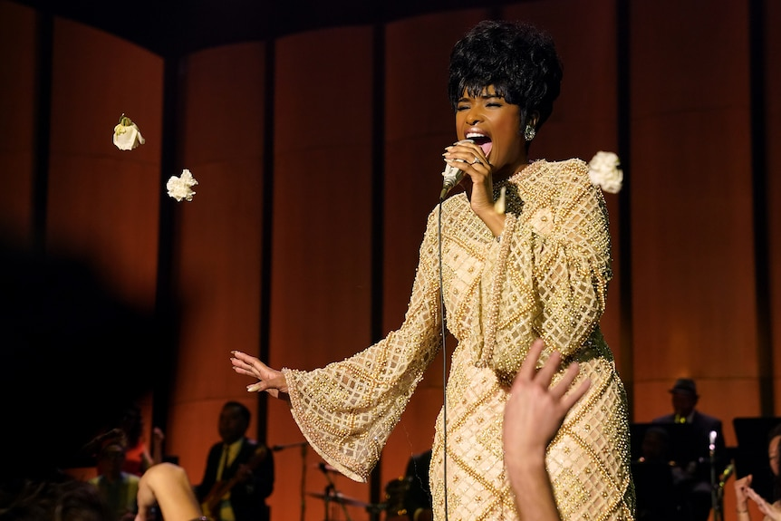 Jennifer Hudson gives an impassioned stage performance, dressed lavishly in sequins which glimmer under a warm spotlight.