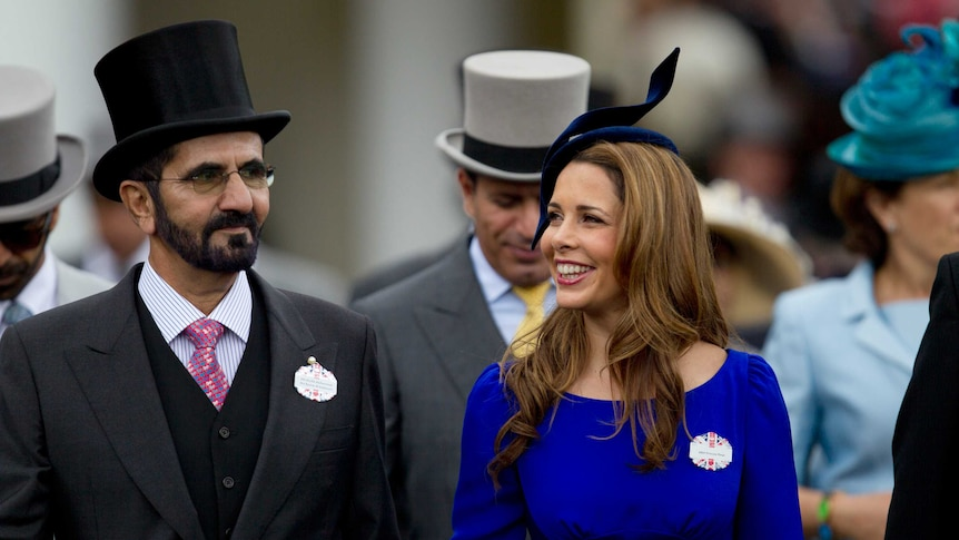 Sheikh Mohammed Al Maktoum and his wife Princess Haya walk towards the paddock dressed for the races.