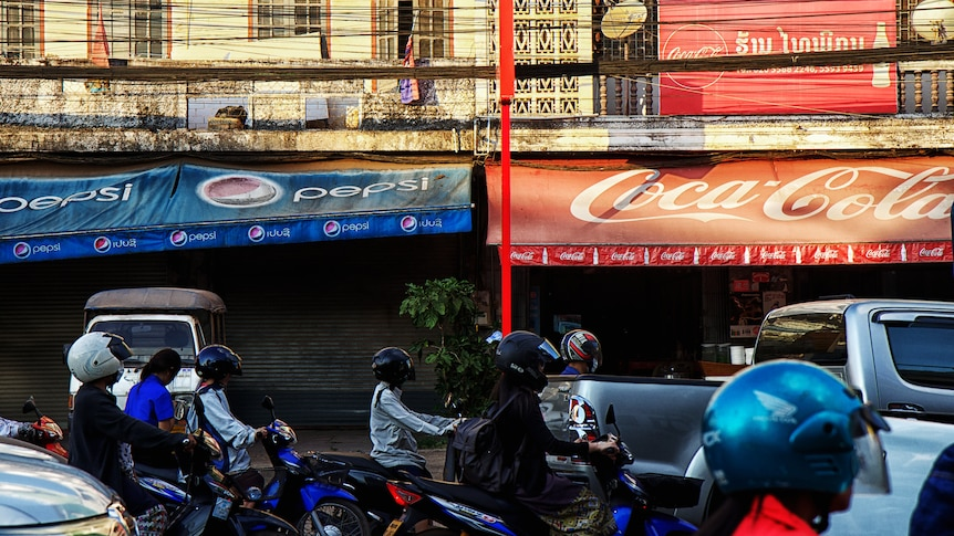Motorcycles and cars queue in traffic in Laos