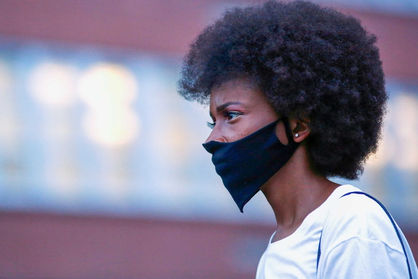 A young black woman in a face mask