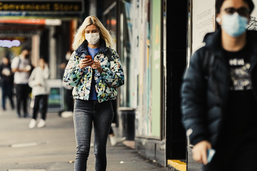 A young woman with a face mask on checks her phone