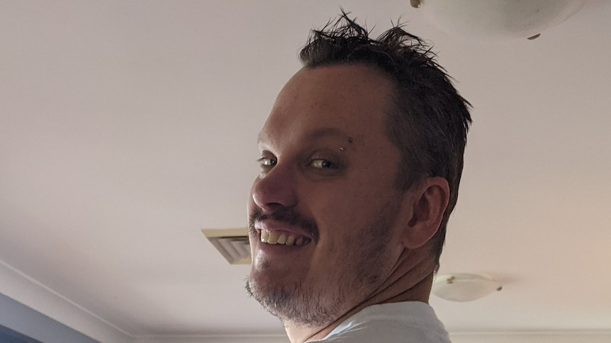 A man with a moustache looks back over his shoulder