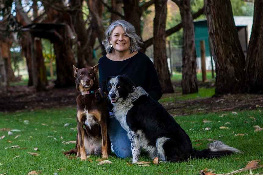 A middle-aged woman with a big smile kneels on the ground with her two dogs.