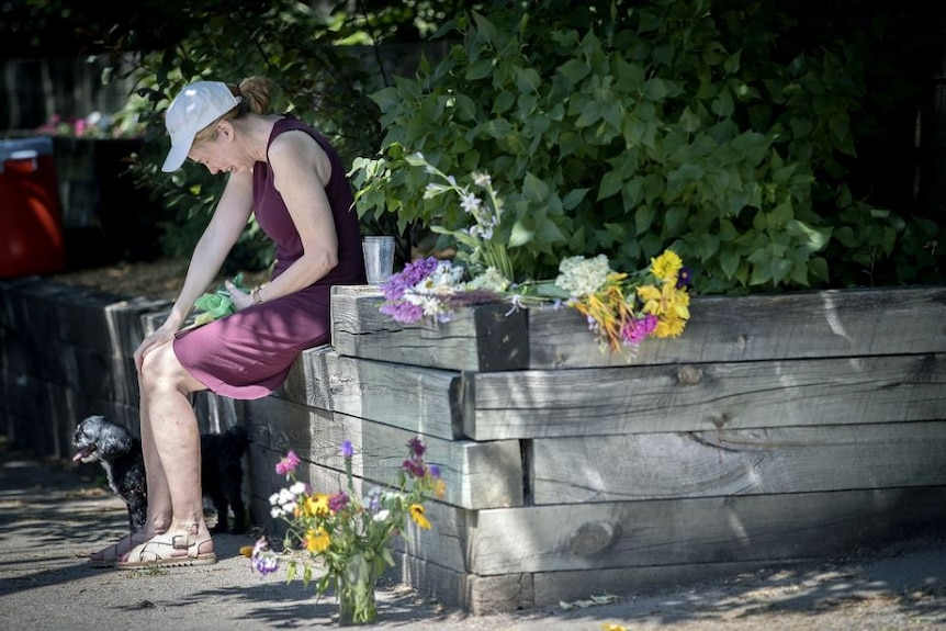 A crying woman sits with her dog surrounded by floral tributes.