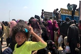 Rohingya refugees including children gather and climb onto a truck in Bangladesh.