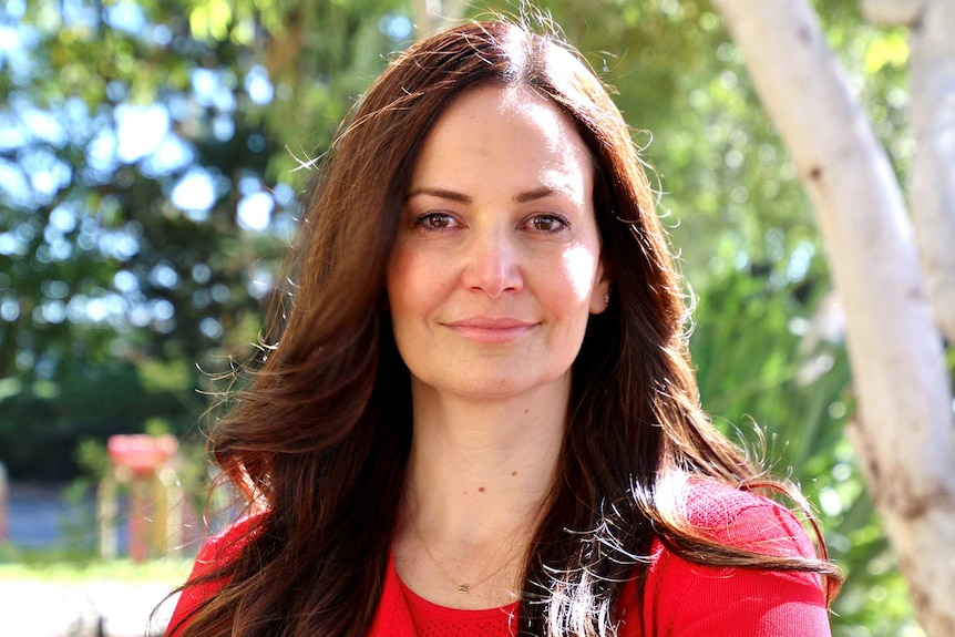 A head and shoulders shot of a woman with long dark brown hair talking in front of trees.