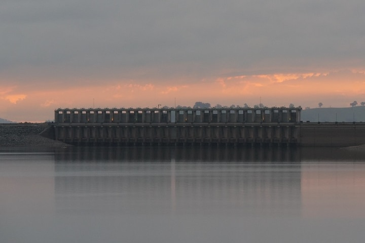 A large dam with the sun low in the sky behind it.
