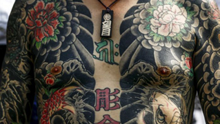 A man shows his traditional full body tattoo, with flower motifs, as he poses outside the Sensoji temple in Tokyo.