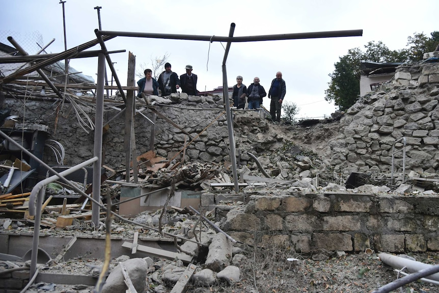 Men look at damage in a residential area after shelling by Azerbaijan's artillery.