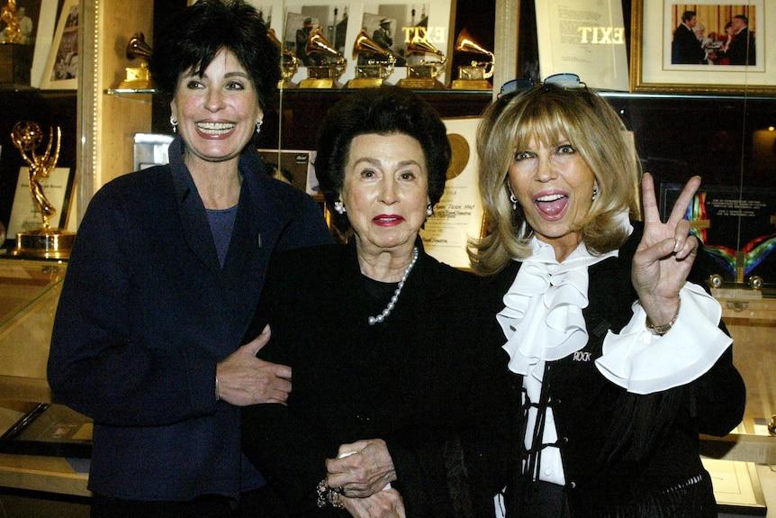 Nancy Sinatra Sr stands between daughters Tina (left) and Nancy Jr (right) in front of memorabilia of Frank Sinatra