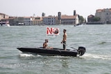 """Two shirtless men aboard a motorboat in Venice with a flag that reads """"no big ships"""" in Italian."""
