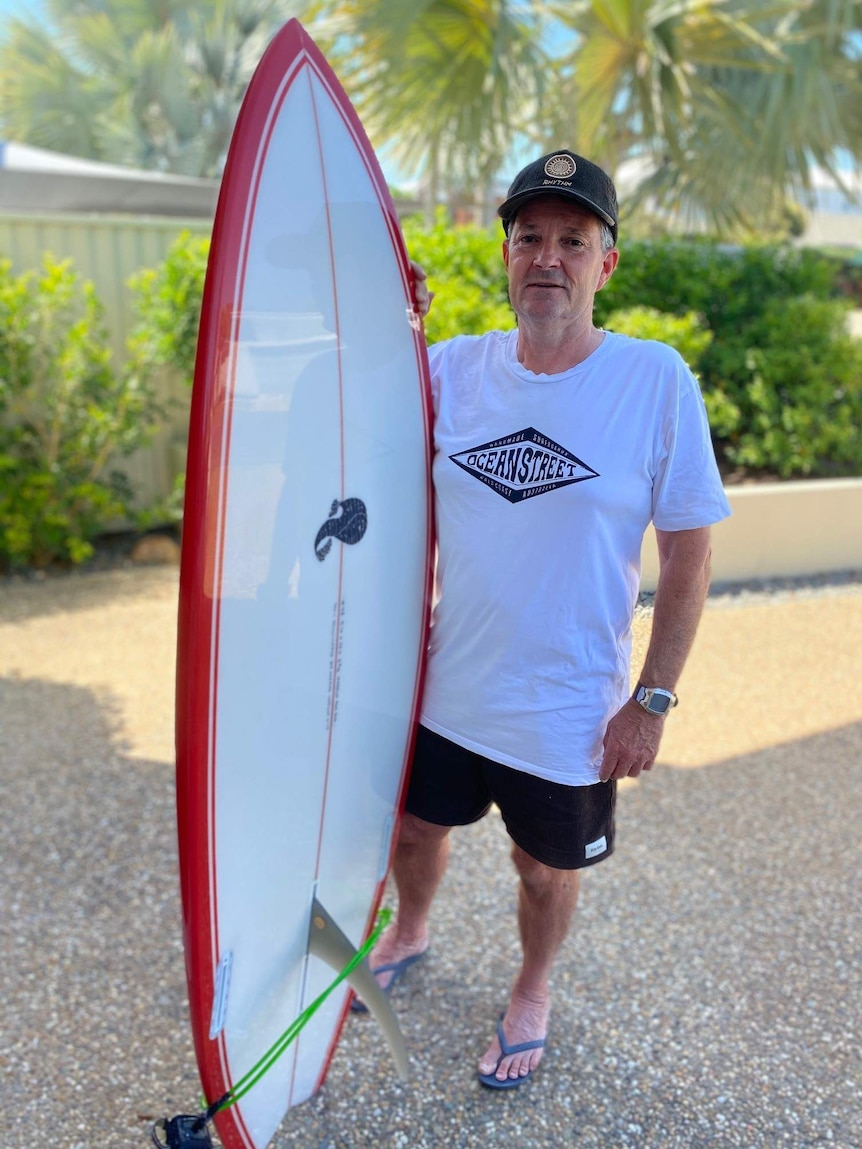 A middle-aged man wearing a baseball cap holds a surfboard with palm trees behind him