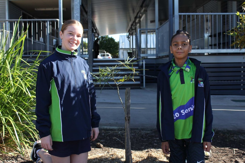 Two children stand either side of a small tree in front of a school demountable