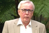 A man in a collared shirt and coat speaking in a garden