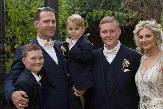 A man and three boys and a woman wearing a wedding gown