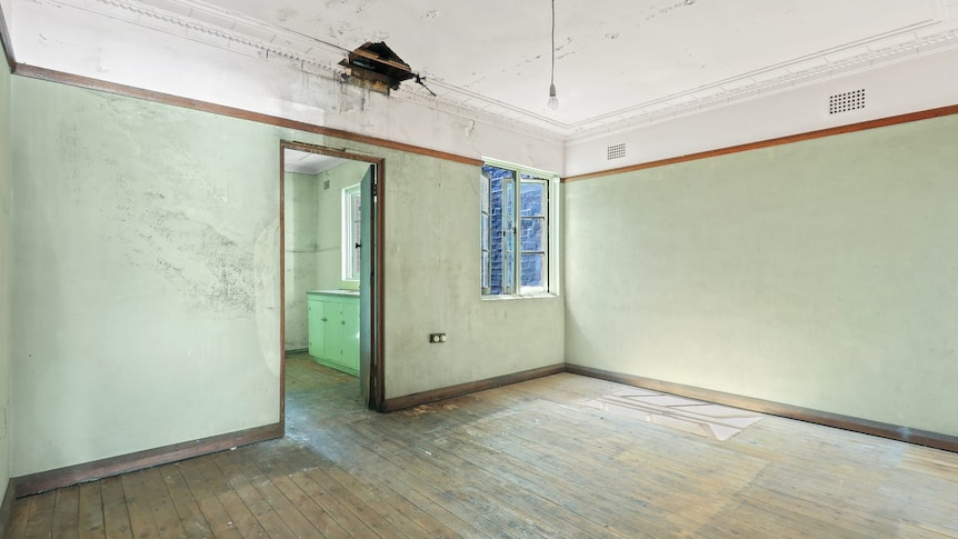 A bare room with a wood floor and a hole in the ceiling