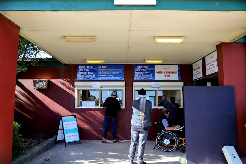 Two men standing and one man in a wheelchair outside a booking window of a racecourse that has signs for COVID-19 vaccinations