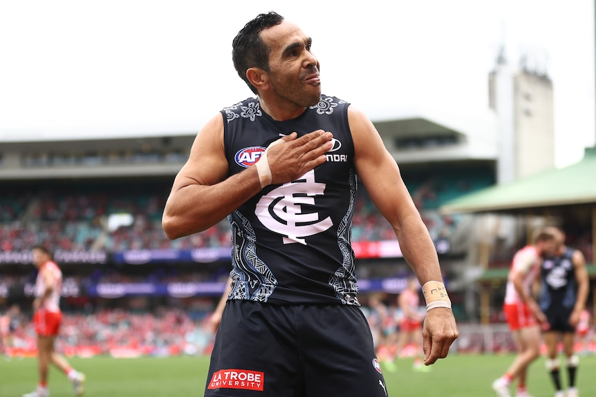AFL player with his hand on his chest after scoring a goal during a match