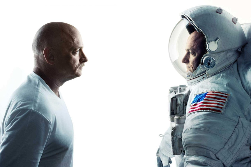 A man in a white shirt facing a man in an American space suit.