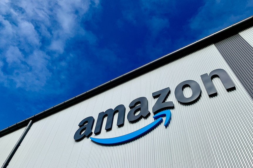 The Amazon logo is shown on the side of a building shot from below, with bright blue sky behind.