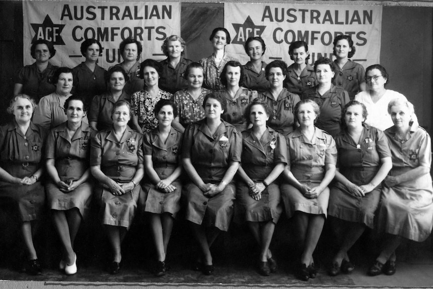 women pose in front of a banner