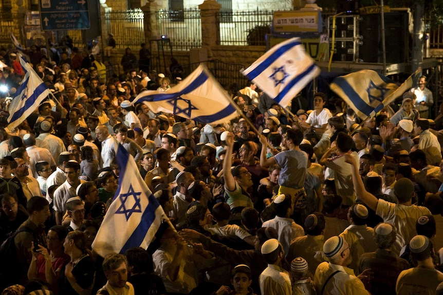 Israeli right-wing activists wave Israel national flag during a rally