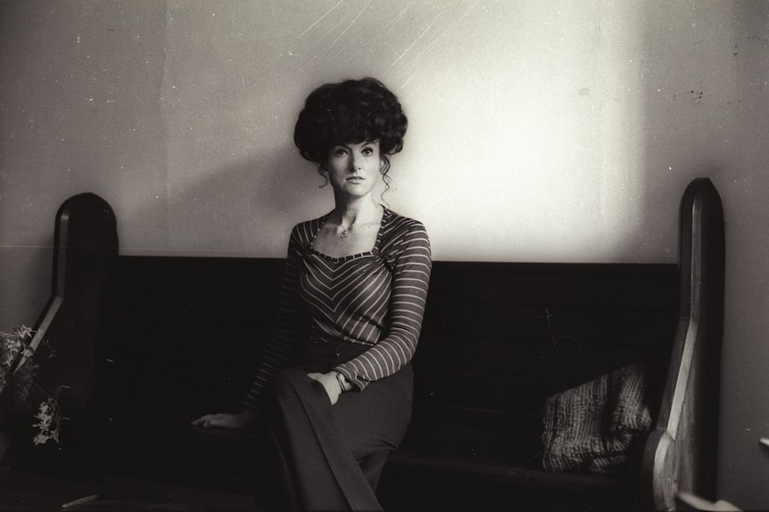 A black and white photo of a woman with a beehive hairdo seated and looking towards the camera.