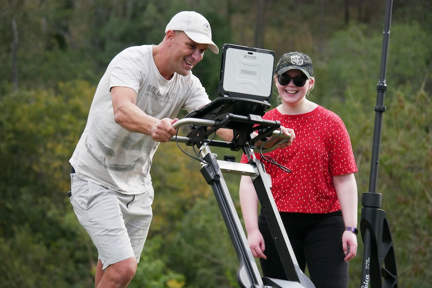 Daniel Thompson smiles as he pushes a Ground Penetrating Radar scanner at Shapcott Park in Ipswich, west of Brisbane.