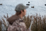 Duck hunter Dean Rundell, flanked by his gun dog Astro, lies in wait in the marsh.