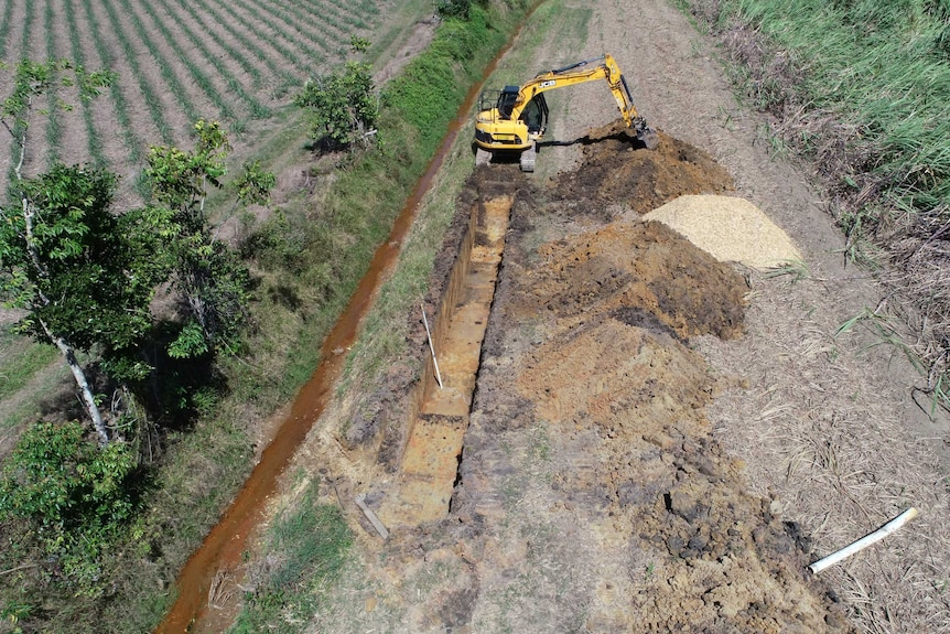 Birds eye view of a mechanical digger carving out a trench in a rural paddock.