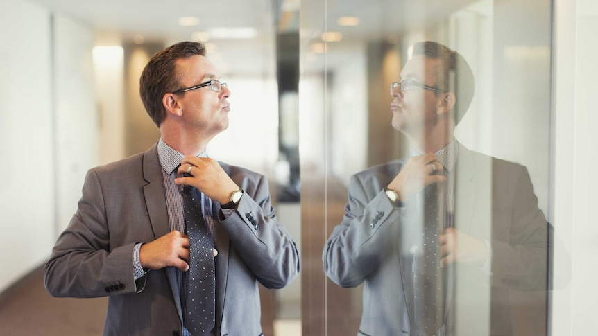 A man in a grey suit fixes his tie in the reflection on a glass wall with a haughty look on his face.