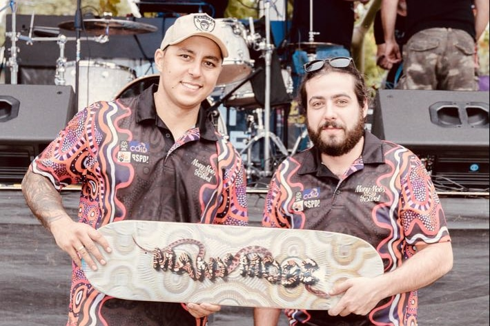 """Two men smile as they both hold a skateboard that says """"Many mobs"""". They are wearing shirts emblazoned with Indigenous art."""