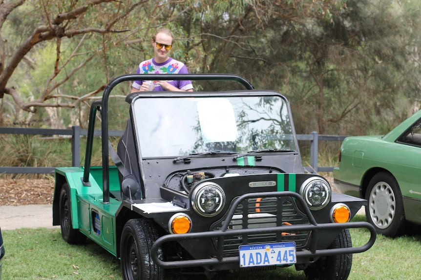 A man wearing a t-shirt and sunglasses stands in the back of a 70s Moke.