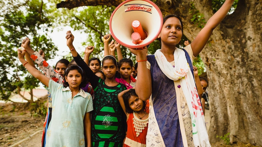 A group of girls in India standing together with their fists held in the air, and one holding a megaphone.