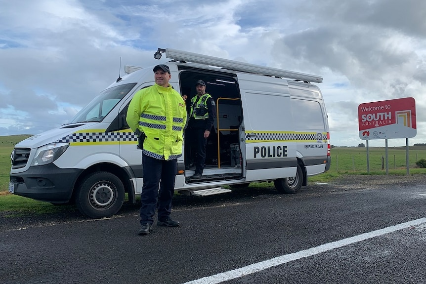 A policeman stands near a van and one inside a van next to a sign about entering South Australia