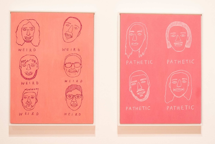 Pink painting of men's faces with words 'weird' and 'pathetic' under each face