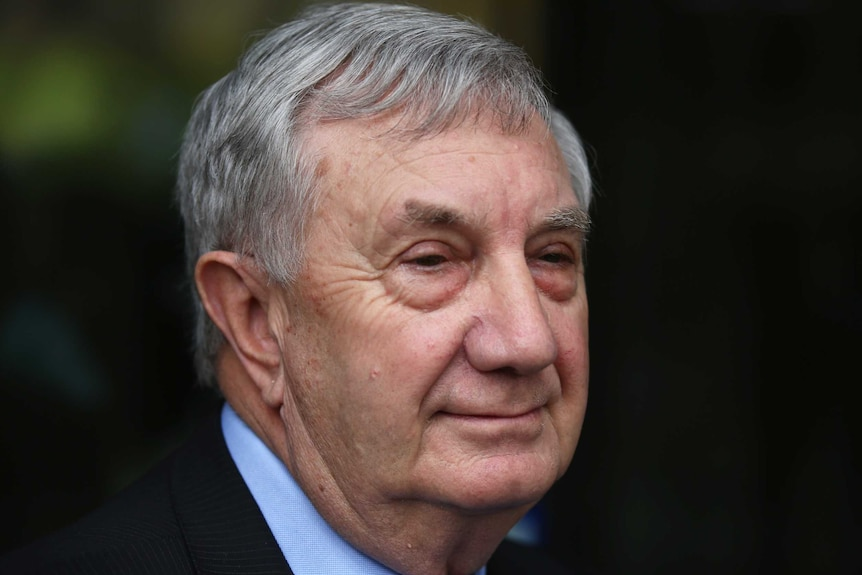 Profile of Mr McKechnie — an older man with greying hair in a suit smiling and speaking to journalists