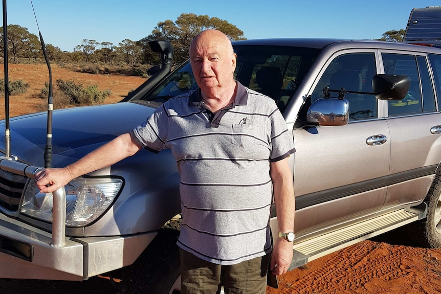 Kevin Kyle is standing by a 4WD in the desert with a serious expression.