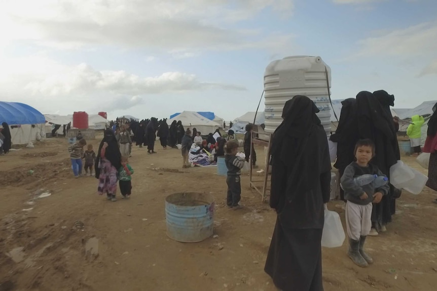 Women and children line up for water at al-Hawl