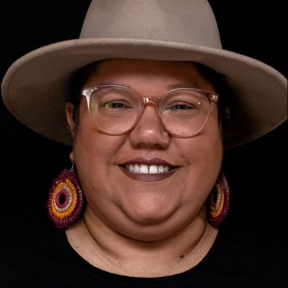 A smiling woman with glasses wears khaki Akubra style hat, background behind her is black.