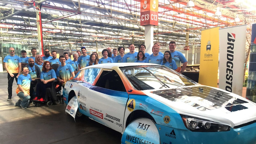 A solar-powered car with a group of students.