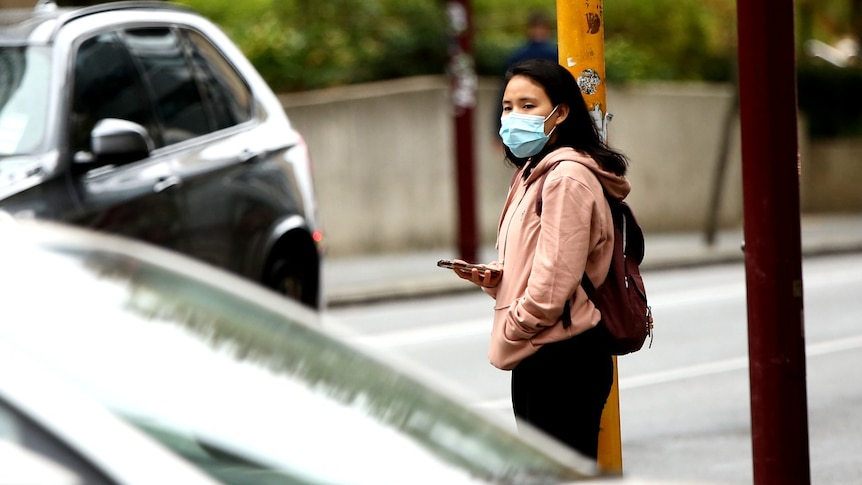 A picture of a woman wearing a hoodie and a mask, carrying a backpack.