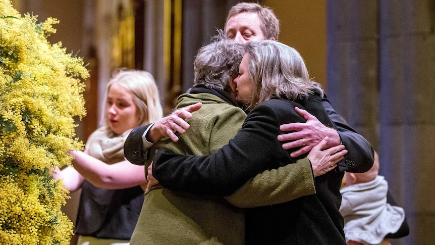 Grieving relatives embrace at the MH17 memorial service in Melbourne