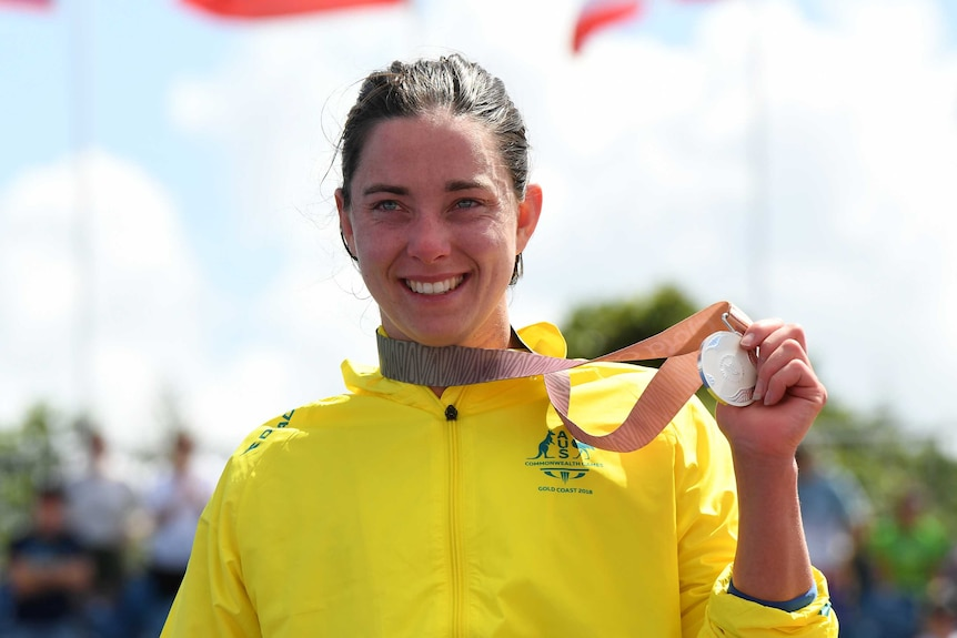 Emily Tapp holds up her silver medal.
