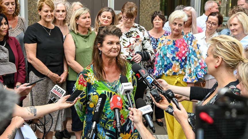 Julie Davis, centre, surrounded by other women involved in the class action suit outside court in Sydney today.